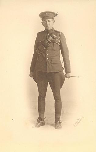 Photo d'un soldat debout, tenant un fouet derrière le dos avec les deux mains.