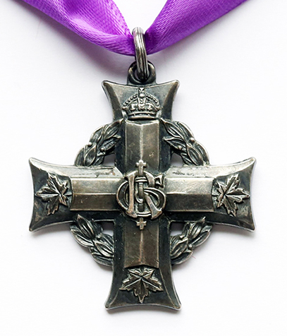 Une croix grecque accrochée à un ruban pourpre par un petit anneau. Une guirlande de laurier sous les bras de la croix. Un chiffre se trouve à l'intersection des deux bras. Une couronne surmonte le bras supérieur; trois feuilles d'érables se trouvent à l'extrémité des autres bras.
