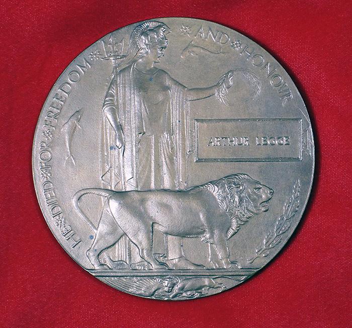 Une plaque de cuivre circulaire représentant l'image d'une femme tenant des feuilles de laurier et un lion devant elle.