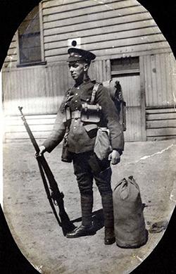 L'image d'un soldat debout dans un passepartout ovale. Il tient son fusil dans la main droite. Un sac marin se trouve à côté de son pied gauche. On peut voir un bâtiment à l'arrière-plan.