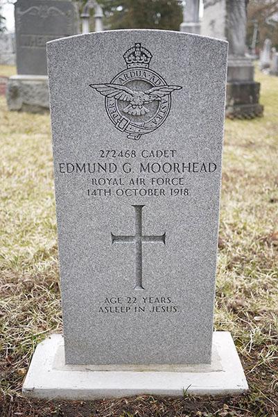 Une pierre tombale avec une croix et un blason montrant un oiseau dans un cercle entouré d'une couronne.