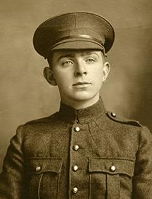 Portrait d'un soldat portant une casquette. On peut remarquer des poches poitrine, des boutons et des insignes de collet.
