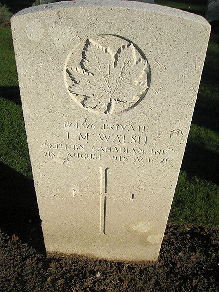 Une pierre tombale avec un ecroix et une feuille d'érable.