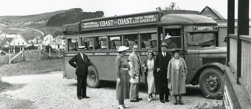 Photographie noir et blanc d'un groupe de personnes devant un autobus voyageur de 1932. Derrière l'autobus, on peut apercevoir quelques maisons du village de Percé et les montagnes qui forment la côte. Sur l'autobus il est écrit : Montreal Vancouver Coast to Coast New York Los Angeles.