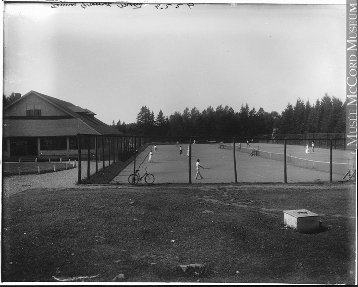 Photographie noir et blanc du terrain de tennis de Métis-sur-Mer. Une haute clôture entoure le terrain de tennis.  Des hommes, vêtu d'un pantalon et d'un chandail blanc, et des femmes, vêtu d'une longue jupe blanche d'une chemise blanche à manche longue et coiffée d'un chapeau, jouent au tennis. Du côté gauche, on aperçoit le bâtiment du club de golf Cascade.