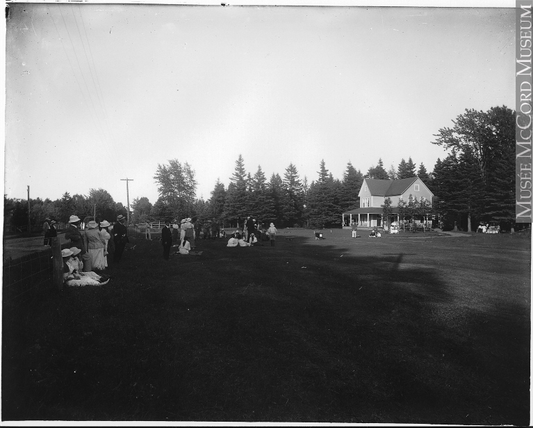 Photographie noir et blanc du départ du parcours du club de golf Cascade. Une vingtaine d'individus vêtue à la mode des années 1914 attendent le départ d'un parcours. Quelques femmes sont assises sur la pelouse. En arrière-plan, un chalet de deux étages à l'architecture victorienne épurée.