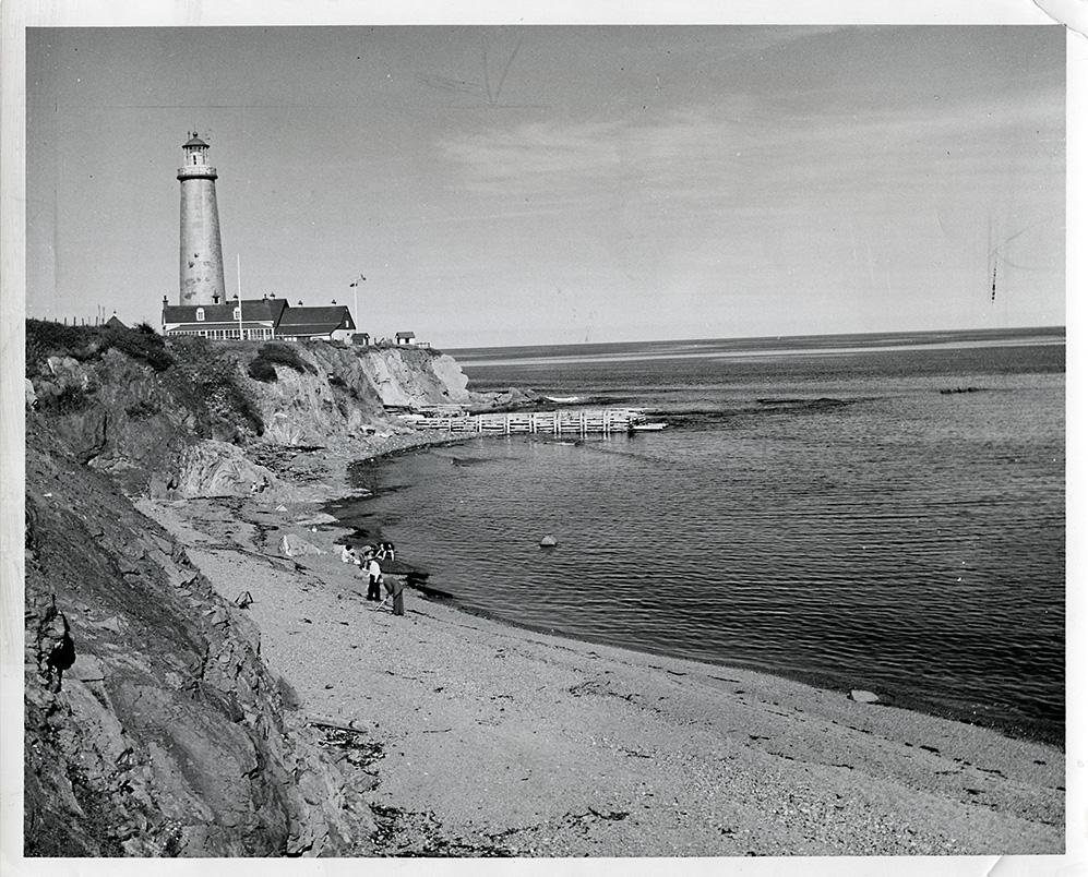 Photographie noir et blanc de du phare de Cap-Des-Rosiers. Dans une baie, une famille cherche des palourdes sur la plage. En arrière-plan, sur un cap rocheux, on aperçoit le phare de Cap-Des-Rosiers.