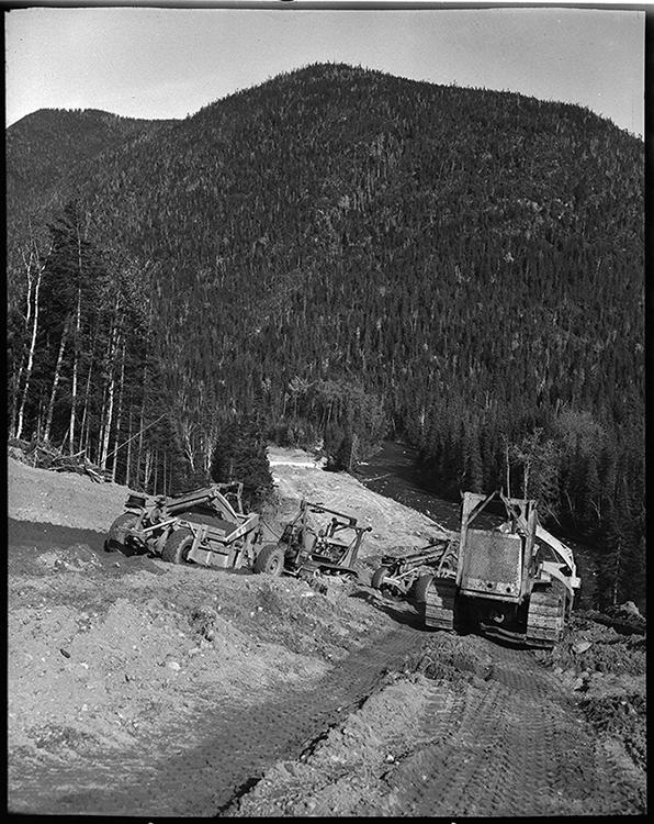 Photographie noir et blanc des travaux sur le chemin Trans-Gaspésien. Dans un paysage forestier, sur une pente abrupte, des travailleurs de la construction manipulent de la machinerie afin de faire les travaux de préparation d'aménagement de la route.