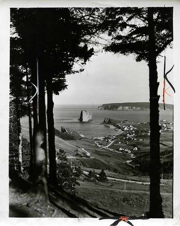 Photographie noir et blanc du Roché Percé. Il s'agit de l'un des points de vue les plus populaires. La photographie est prise en hauteur, a une distance éloignée du Rocher, ce qui donne une vue à la fois sur le village de Percé, l'Île de Bonaventure et le Rocher Percé. Les arbres des deux côtés de la photographies créent un cadre naturel autour de ce paysage.