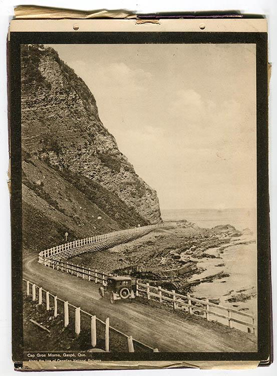 Photographie sépia d'une voiture circulant sur le Boulevard Perron, une route de gravier serpentant au pied d'un immense cap rocheux, passage étroit entre la falaise et la mer. Une simple barrière en bois sépare la route du rivage