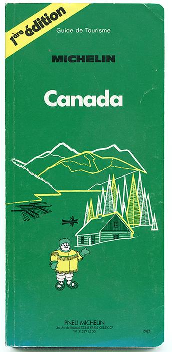 Page couverture de la première édition du guide Michelin. Sur un fond vert foret, la mascotte des pneus Michelin est vêtue d'un manteau à frange. Il porte des raquettes un chapeau en fourrure. Derrière lui un chalet en bois rond dans une forêt de conifères près d'un lac sur lequel il se trouve un canot et des billots de bois. En arrière-plan, les montagnes se succèdent.