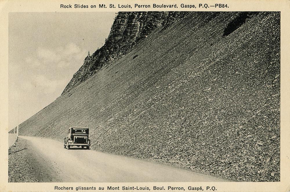 Photographie noir et blanc d'une voiture roulant sur le boulevard Perron. La route longe une pente abrupte tapissée de rochers plats, laissant l'impression d'un éboulement récent.
