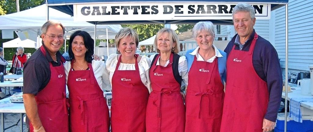 Plan d'ensemble de six personnes portant des tabliers rouges se tiennent debout devant une tente pour la vente de galettes de sarrasin.