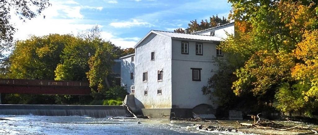 Un bâtiment blanc à toit en pente. Un pont en bois surplombe la digue de la rivière qui se trouve à l'avant-plan.