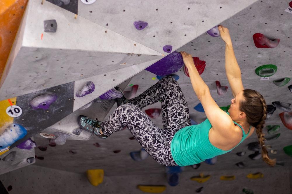 Jeune femme utilisant ses mains et ses pieds afin de rester accroché à des prises ressemblant à des poignées sur un mur artificiel.
