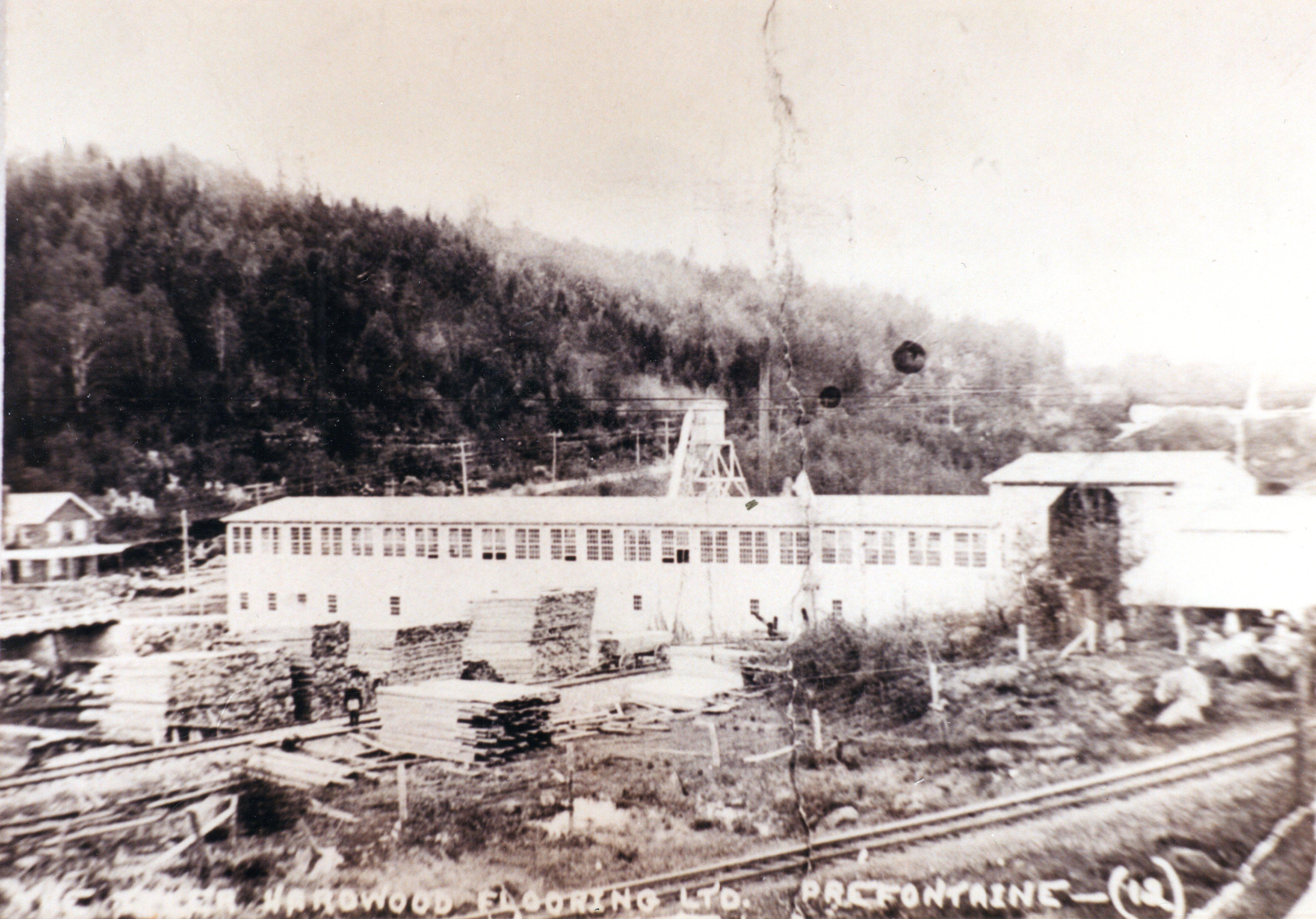 Photographie ancienne montrant les piles de planches de bois auprès des voies ferrées et des moulins à bois de la Tyler Hardwood Flooring à Préfontaine en 1923.