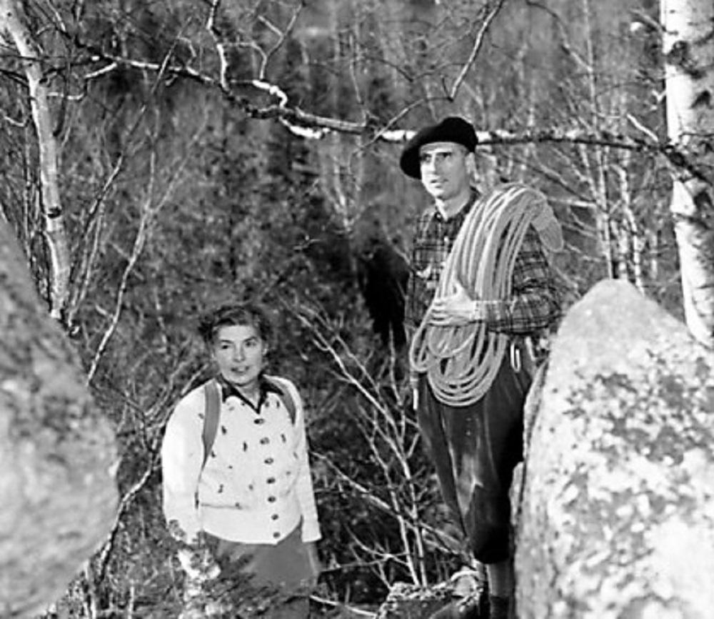 John Brett et son épouse en 1947, dans la forêt; John, un béret sur la tête, tient une corde d'escalade.