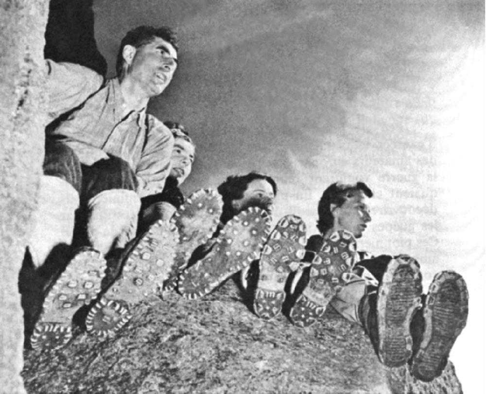 Quatre personnes assises sur le sommet d'un rocher.