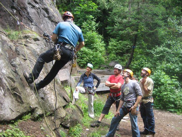 Groupe de cinq personnes; un homme attaché à faible hauteur sur une paroi; trois hommes et une femme au sol l'observent.