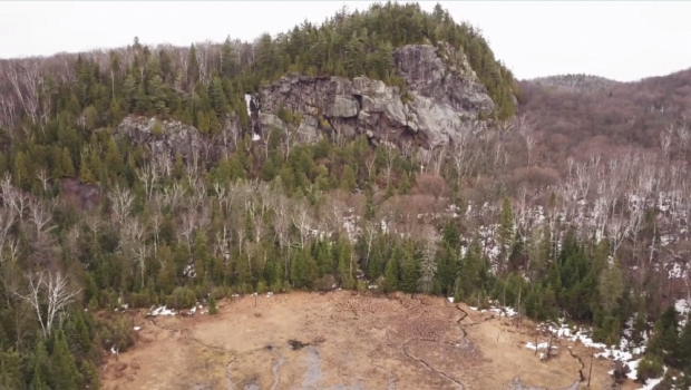 Plan éloigné d'une montagne, ses arbres et ses parois rocheuses bien visibles.