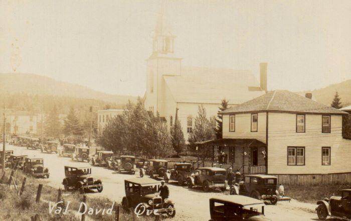 Vue du village avec rue principale, église et vieilles voitures