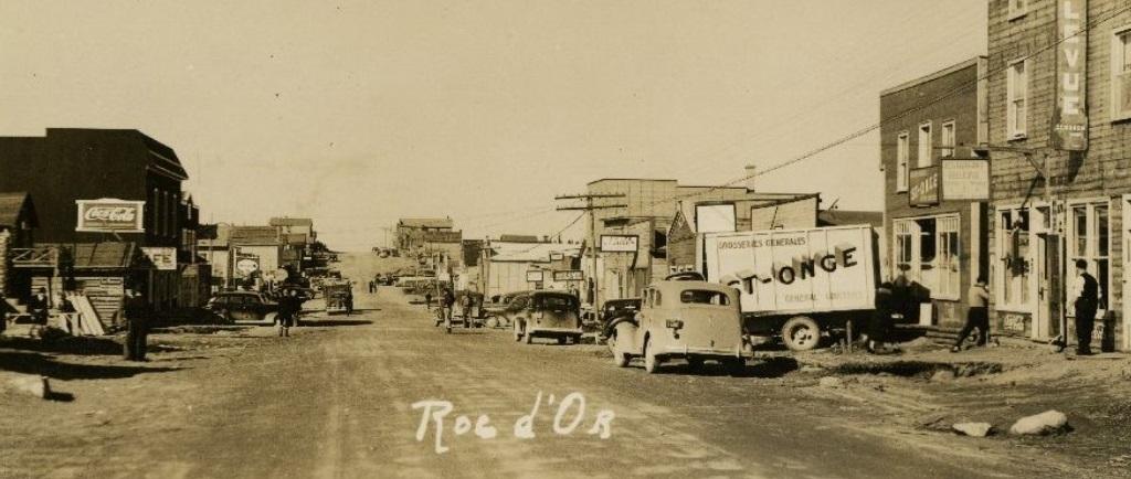 Photographie sépia d'une rue non pavée bordée de bâtiments des deux côtés. Du côté droit, plusieurs voitures et un camion portant l'inscription « St-Onge » sont visibles.