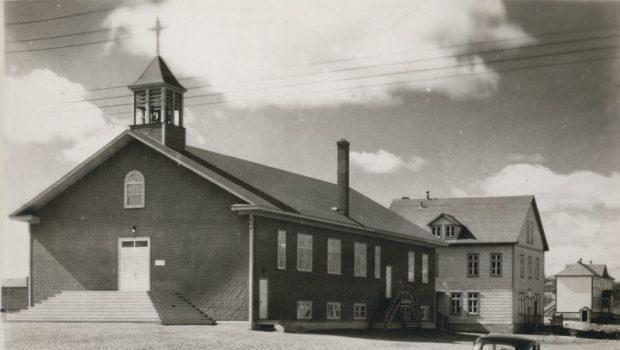Photographie en noir et blanc d'une église recouverte de papier goudronné et surplombée d'un clocher dont la croix se confond avec les nuages. À l'arrière, un presbytère de planches de trois étages.