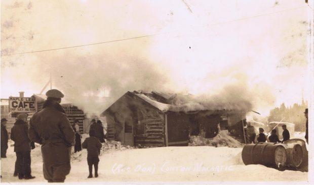 Photographie en sépia d'une cabane en bois rond alors qu'elle est incendiée. Un large nuage de fumée occupe la moitié supérieure de la photo. Une douzaine de curieux assiste à la scène. À gauche, l'enseigne « Maple Leaf CAFE Chop Suey and Rooms ».