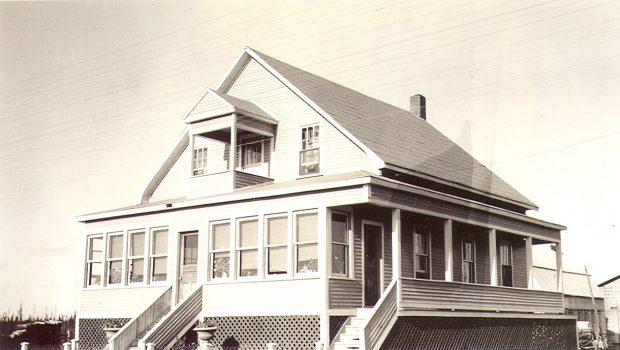 Photographie en sépia d'une belle résidence de deux étages. Il y a de nombreuses fenêtres en façade et une galerie à droite. Un petit balcon à l'étage. À l'arrière-plan, une étable et un garage.