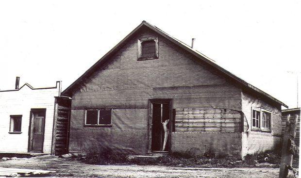 Photographie en noir et blanc d'un bâtiment recouvert de papier goudronné, dont une partie est arrachée. Quatre fenêtres, deux sur le côté droit et deux devants, sont visibles. Une cabane en bois rond avec façade de style Boomtown à gauche.