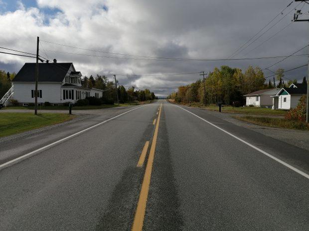 Photographie en couleur d'une route en asphalte avec quelques résidences sur les côtés. À gauche, une maison blanche de deux étages et deux résidences à droite. Le ciel est nuageux.