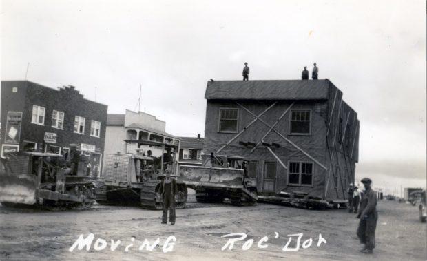 Photographie en noir et blanc d'un bâtiment de deux étages déplacé par trois tracteurs. Plusieurs hommes sont sur le toit. Plusieurs curieux assistent à la scène. À l'arrière-plan, plusieurs immeubles.