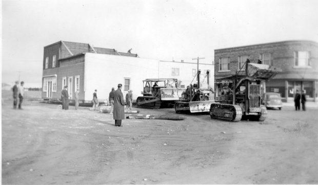 Photographie en noir et blanc d'un bâtiment de deux étages tiré par trois tracteurs. Les billots servant à rouler l'édifice sont déposés devant. Une personne est sur le toit. Plusieurs curieux assistent à la scène.