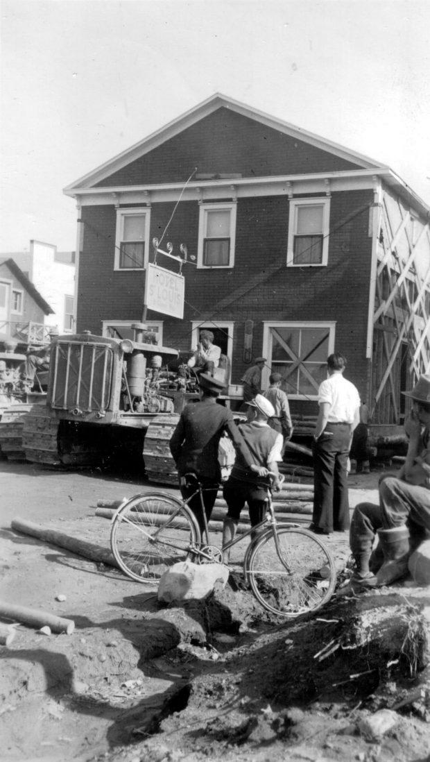 Photographie  en noir et blanc d'un bâtiment de deux étages déplacéer par un tracteur. Plusieurs curieux, dont un avec sa bicyclette, assistent à la scène.