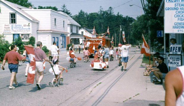 Un camion de pompier décoré mène un défilé d'enfants à vélo et d'adultes qui brandissent des drapeaux canadiens.