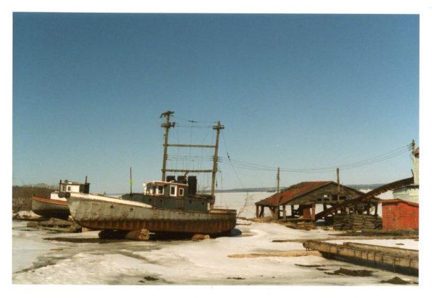 Deux vieux remorqueurs reposent sur des billes de bois à côté d'un hangar de bois délabré au bord de l'eau en hiver.
