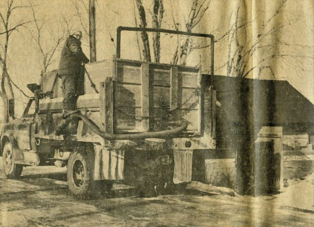 Une coupure de journal montre un homme en train de pomper de l'eau dans son camion à l'aide d'un tuyau.