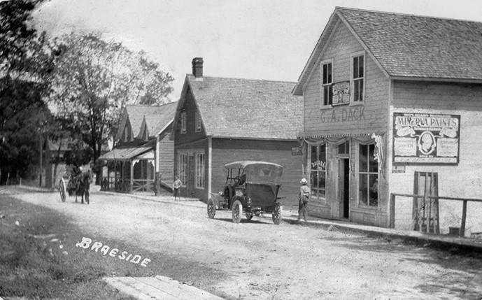 Carte postale d'une scène de rue de Braeside, avec quelques villageois, des commerces, une calèche et une voiture ancienne.