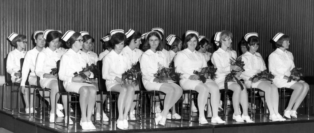 Plus de 20 femmes en uniforme d'infirmière complet assises sur une scène et tenant des fleurs.