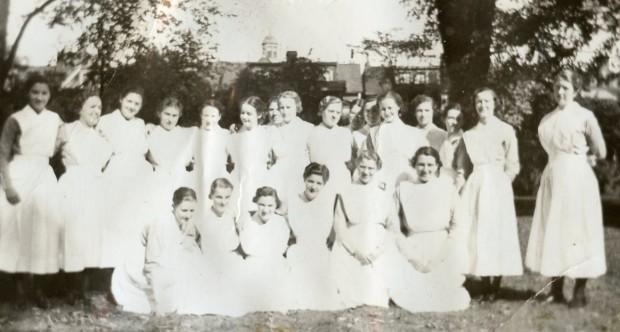 Plus de 20 femmes en uniforme d'infirmière, mais sans la coiffe, sourient à l'extérieur, debout ou à genoux.