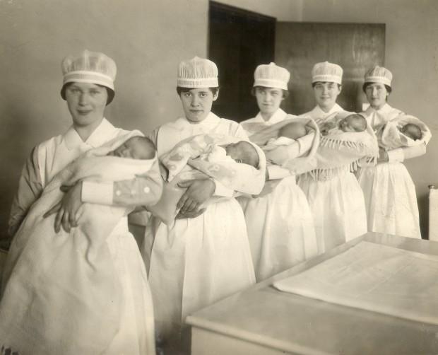 Cinq jeunes femmes tiennent des bébés emmitoufflés et posent pour la photo. Elles portent des coiffes d'infirmière.