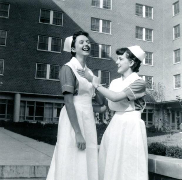 Deux jeunes femmes portant l'uniforme et la coiffe d'infirmière plaisantent affectueusement devant un grand immeuble en briques.