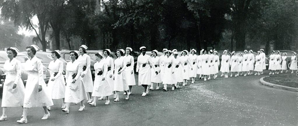 Plus de 30 femmes marchent en rangée, portant uniforme, coiffe et souliers blancs.