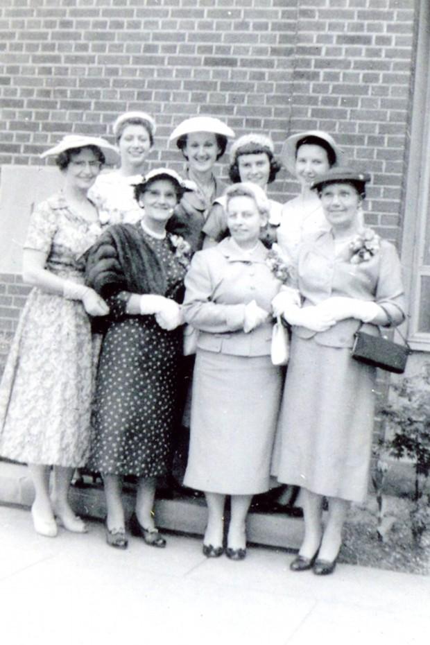 Huit femmes posent pour une photo. Elles sont habillées élégamment, portant jupes longues, chemisiers, talons hauts et chapeaux. Des fleurs sont épinglées à leur poitrine.