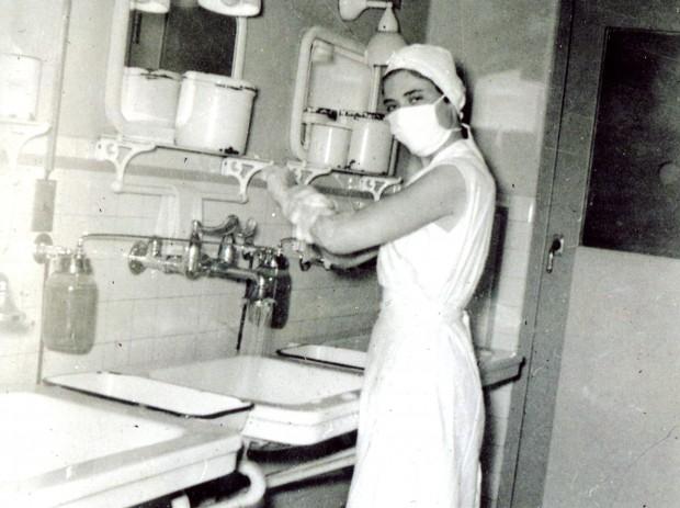 Une jeune femme se savonne jusqu'aux coudes au-dessus d'un évier. Elle regarde l'appareil photo, et l'on voit qu'elle sourit malgré le masque chirurgical. Elle porte divers éléments de l'uniforme d'infirmière, bien qu'elle n'ait pas de manches. Ses cheveux sont complètement couverts par un bonnet protecteur.