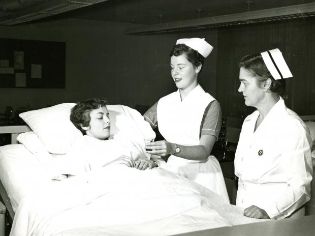 Une jeune femme en chemise d'hôpital se repose au lit pendant qu'une autre, vêtue d'un uniforme d'infirmière, lui tend un petit verre. Une autre femme portant un uniforme et une coiffe d'infirmière observe.