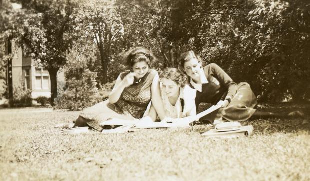 Trois jeunes femmes habillées de façon décontractée étudient dans un parc.