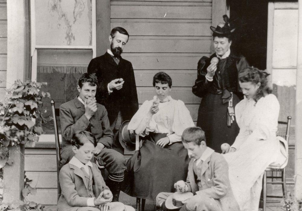 Photo en noir et blanc montrant une famille assise sur une véranda : un homme, deux femmes, une fille et trois garçons qui regardent tous la pomme qu'ils tiennent à la main.