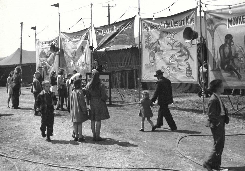 Une photo en noir et blanc d'une foule à une fête foraine parmi de nombreuses tentes; on voit un carrousel en arrière-plan