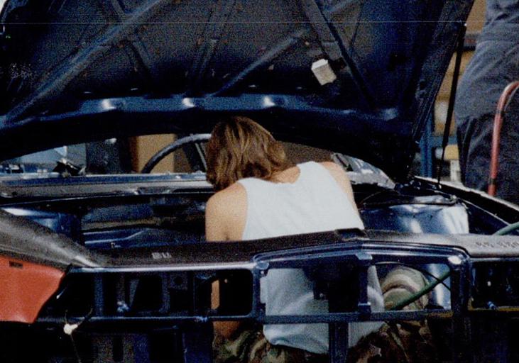 Image en couleur représentant trois hommes utilisant des machines-outils pour assembler une voiture sur une chaîne de montage.